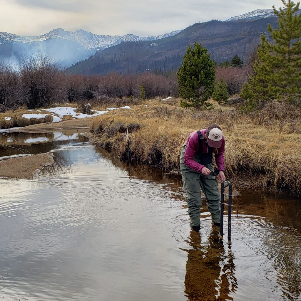 Woman in waiters stands in a stream while using a hammer and level to adjust stream monitoring station equipment in a mountain valley. Grey smoke can be seen in the background, rising off of the mountainside.