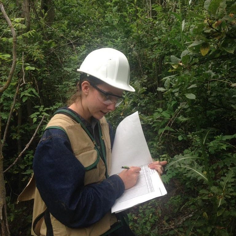 An ecologist in hard hat, goggles, and brown utility vest stands in a forest and writes notes in her field journal.